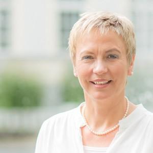 Typ-und Imageberaterin -Frau mit kurzen blonden Haaren und weißem Oberteil
